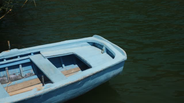 empty lonely old blue wooden rowing boat moored