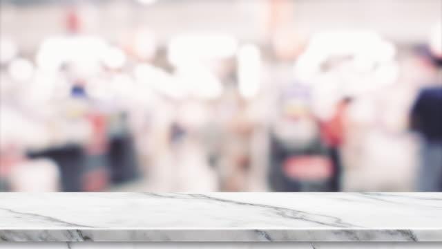 stockvideo's en b-roll-footage met lege marmeren tafel en wazig mensen winkelen bij supermarkt lichte achtergrond. mock up achtergrond sjabloon voor display.promotion productpodium. - marmer