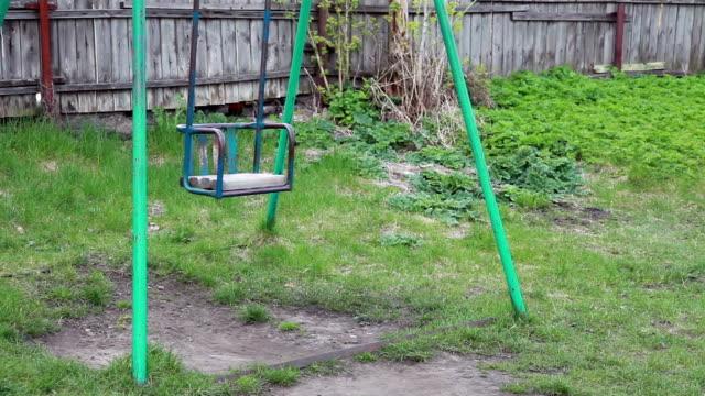 Balançoire métal vide, se balançant dans l'arrière-cour - Vidéo