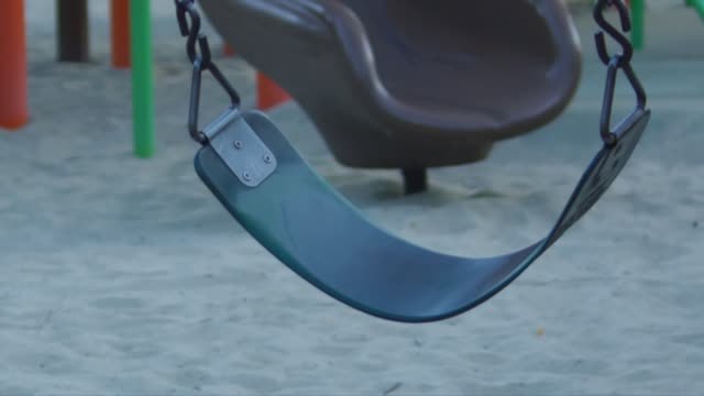 Empty moving swings at a playground video