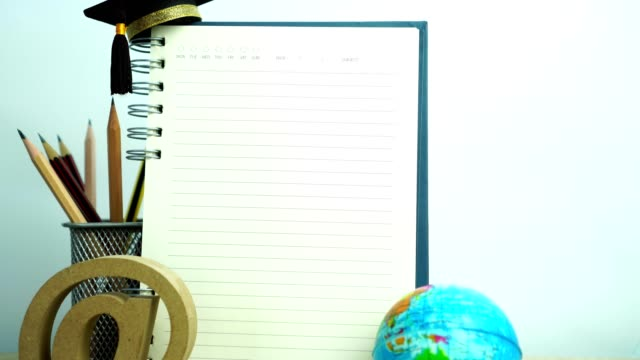 Empty notebook mockup for your image text with pencils, world globe, e-mail sign, graduation hat on white background. Concept of global business study abroad educational. Back to School.