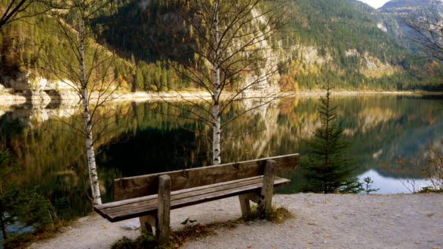 vídeos de stock, filmes e b-roll de banco velho vazio em uma costa do lago de langbathsee em áustria salzkammergut no dia ensolarado do outono - áustria