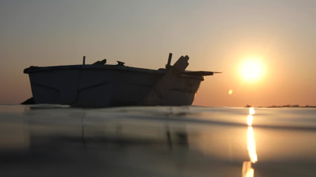 Empty old wooden boat floating on open sea during sunset