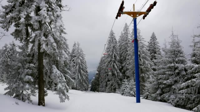 Empty old-school colorful retro single chair lift moving between forest snow trees in winter on Pancir hill in Sumava Czech republic