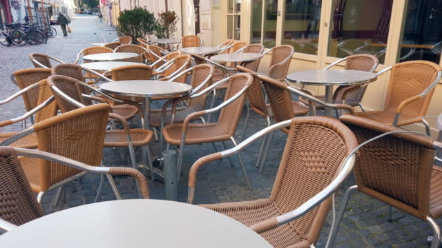vídeos de stock e filmes b-roll de empty outdoor dining chairs during coronavirus epidemic lockdown - covid restaurant