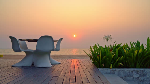 empty outdoor patio chair and table with sea beach background - vídeo