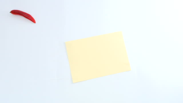 Empty piece of paper and red peppers are moving to center on white background video