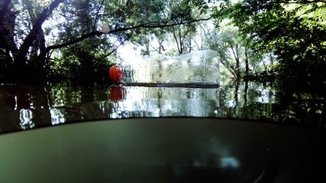 vídeos de stock e filmes b-roll de empty plastic bottle floating on flooded river - sem higiene
