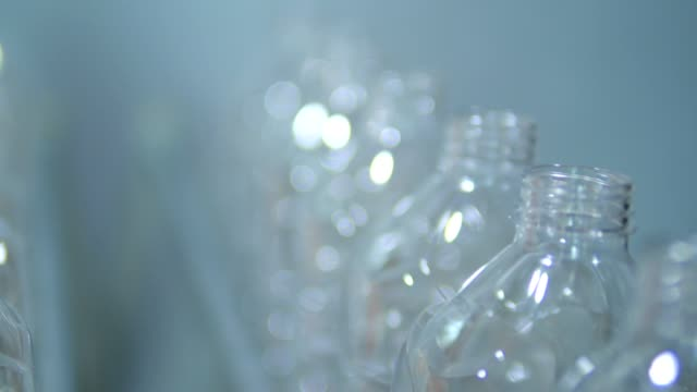vídeos de stock, filmes e b-roll de os frascos plásticos vazios movem-se através da linha de fábrica - garrafa