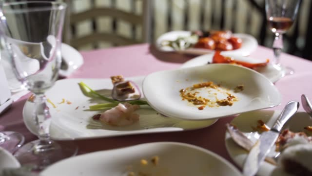 Empty plate after eating food. With fork and knife on it. Empty plate after eating food. With fork and knife on it. Wasted food on festive table after dinner party leftovers stock videos & royalty-free footage