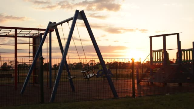 empty playground - sunset. swings swaying. - struttura pubblica video stock e b–roll