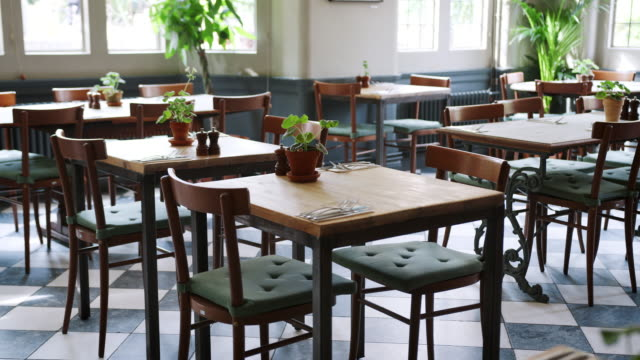 Empty Restaurant Interior With Tables Set For Service View of empty restaurant interior with tables and chairs set for service barren stock videos & royalty-free footage