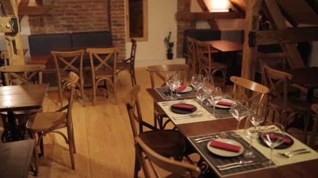 vídeos de stock e filmes b-roll de empty restaurant with table set for diner party - mesa mobília