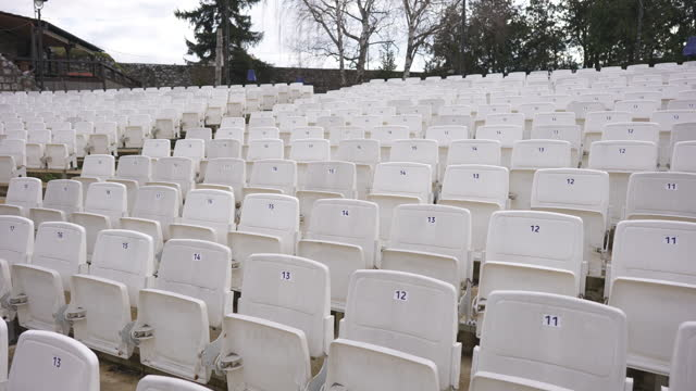 Empty rows of numbered white foldable chairs at the auditorium