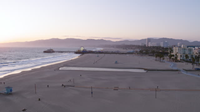Empty Santa Monica Beach During Covid-19 Pandemic Aerial shot of Santa Monica Beach and Pier which are currently closed due to the Covid-19 pandemic. These areas are never empty. lockdown viewpoint stock videos & royalty-free footage