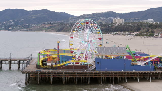 Empty Santa Monica Pier During Covid-19 Pandemic Aerial shot of the famous Santa Monica Pier, a famous tourist attraction in Los Angeles, California. The pier is currently closed due to the Covid-19 Pandemic western usa stock videos & royalty-free footage