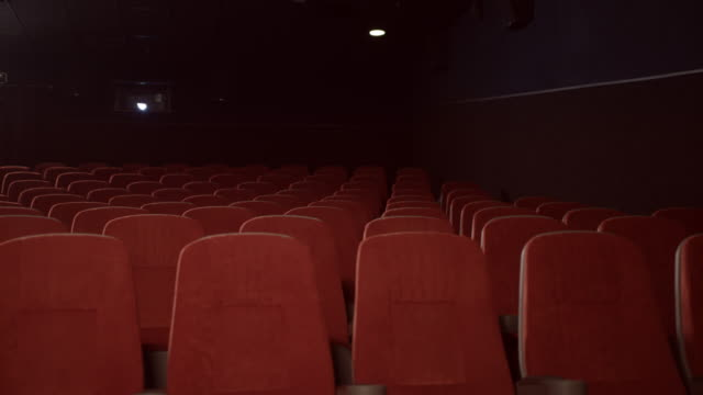 Empty seats in cinema theatre. Empty theatre hall with red armchairs