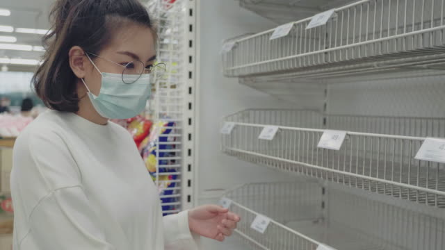empty shelves of the store sale of goods. Sale shop sale empty storefronts Asian woman looking at many empty shelves with few canned goods left in a Bangkok supermarket because of panic shopping because of Covid-19 virus. Thailand. market retail space stock videos & royalty-free footage