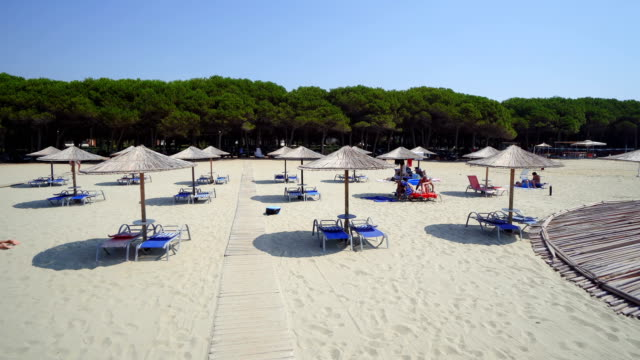 Empty Sunny Beach with Umbrellas, Sun Beds on the Ionian Sea. The coastal resort line, where people relax and sunbathe