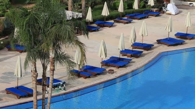 leeren swimmingpool in den frühen morgenstunden im hotel in der nähe von rotes meer, ägypten - sonnenschirm stock-videos und b-roll-filmmaterial