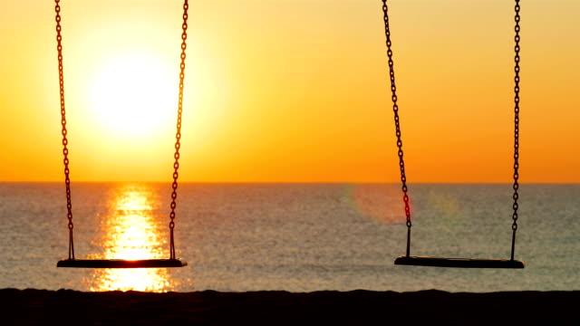 leere schaukel bei sonnenuntergang am strand - schaukel stock-videos und b-roll-filmmaterial