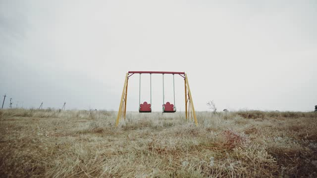 Empty swing in the field. Abandoned city. Desolate playground. Deserted place.