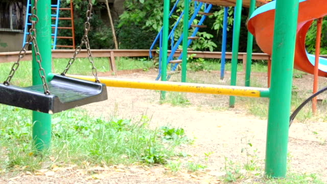 Empty swing swaying at playground video