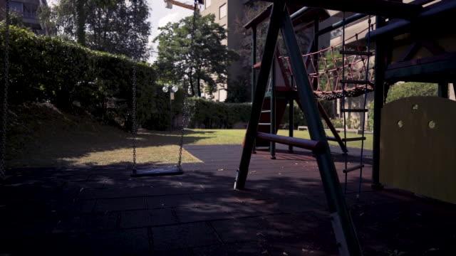 vídeos y material grabado en eventos de stock de vacíe los columpios a cámara lenta en el moderno parque infantil rodeado de árboles verdes al atardecer. concepto de infancia de barrio urbano. - patio de colegio