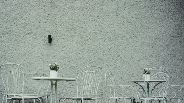 empty tables and chairs against wall - figura femminile video stock e b–roll