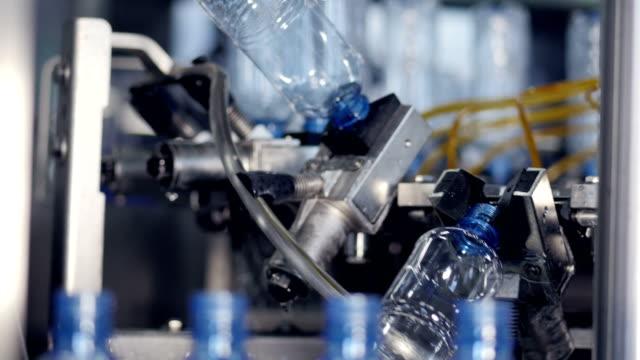 tomma vattenflaskor tog från en transportör linje av en rengöring roterande hjul. 4k. - pet bottles bildbanksvideor och videomaterial från bakom kulisserna
