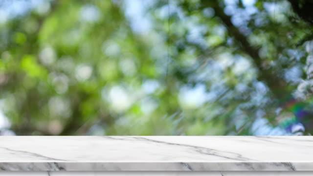 緑の木と公園光背景のボケ味は、反射虹と空の白い大理石のテーブルをぼかし、製品や設計、食品表示用の背景テンプレート スタンド モックアップ - デッキ点の映像素材/bロール