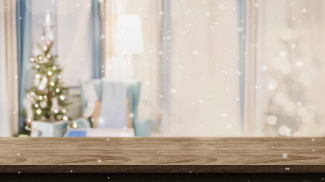 vídeos de stock e filmes b-roll de empty white wood table top and snow falling with blur christmas tree bokeh light background,backdrop template for display of product or design,food stand mock up - living room background
