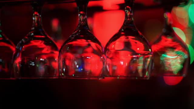 Empty wine glasses above a bar rack.