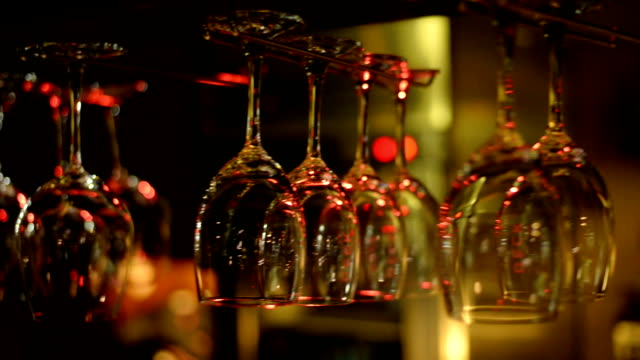 empty wine glasses hang above a bar rack - bicchiere vuoto video stock e b–roll