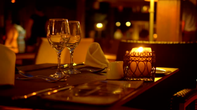 Empty wine glasses on a table in a restaurant at night in 4k slow motion 60fps video