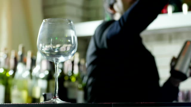 empty wineglass close-up stands on table and guy barman does tricks with bottles video