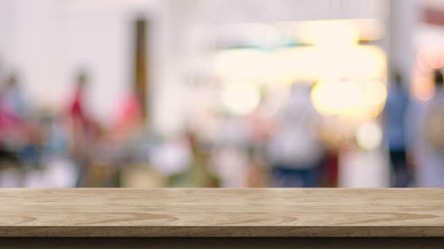 空の木製テーブルの上ぼかしボケ明るい背景と貿易イベント、製品のデザイン、屋台模擬表示用の背景テンプレートでのショッピングの顧客 - 展示会点の映像素材/bロール