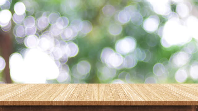 Empty wood table top with blur green tree at park bokeh light background,Backdrop template for display of product or design,food stand mock up