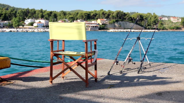 Empty wooden folding chair on pier with few fishing rods video