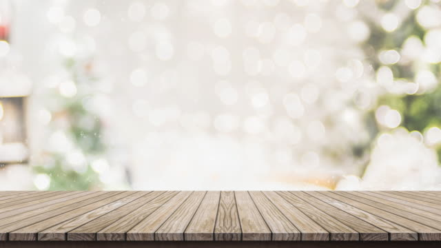 Empty wooden table top with abstract warm living room decor with Christmas tree string light blur background with snow,Holiday backdrop for display of advertise product