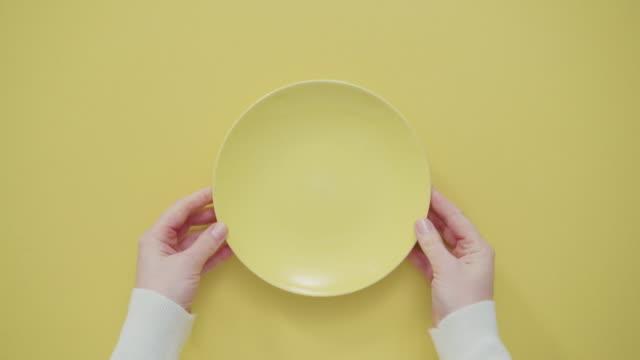 töm gul plåt på gul bakgrund. - empty plate bildbanksvideor och videomaterial från bakom kulisserna