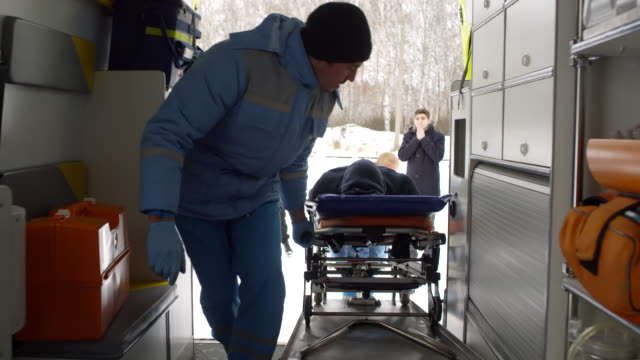 emts loading man on stretcher into ambulance - first responders стоковые видео и кадры b-roll