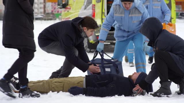emts running towards unconscious man lying on snow - first responders filmów i materiałów b-roll
