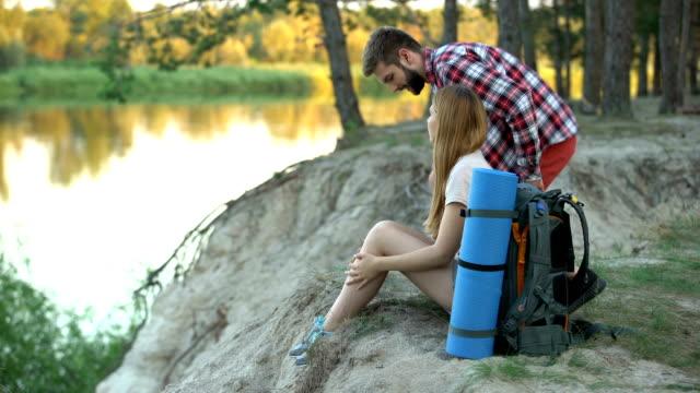 влюбленный в кемпинг рюкзаки сидя и глядя на реку, бежать из города - турист с рюкзаком стоковые видео и кадры b-roll
