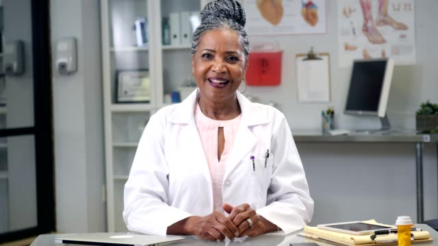 encouraging senior african american female doctor consults with patient via video conference - telemedicine stock videos & royalty-free footage