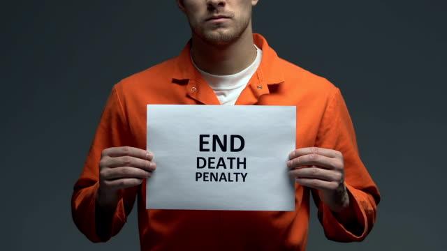 end death penalty phrase on cardboard in hands of caucasian prisoner, protest - wine filmów i materiałów b-roll