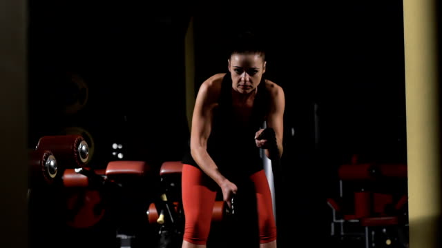 Endurance. Muscular woman exercising with rope in cross training gym video