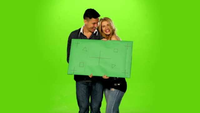energetic and  beautiful Couple holding up a blank sign, green screen video