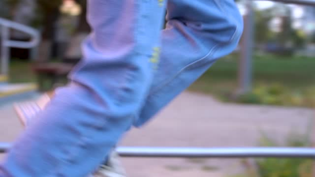 Energetic cheerful girl in jeans and sneakers runs fast in slow-motion close-up.