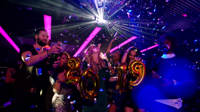 Energetic group of friends celebrating new year 2019 with confetti Stylish group of young multi-ethnic party friends celebrating their new years eve 2019 together at a trendy club, dancing till midnight with confetti and disco lights in the background. new year's eve stock videos & royalty-free footage